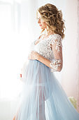 Pretty smiling pregnant girl is wearing blue boudoir dress sitting in bed