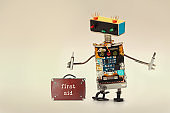 First aid kit and handyman service worker with screwdrivers. Fun toy robot, colorful head red blue light bulbs eyes gradient background