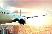 passenger plane flying over city building and sun light on background