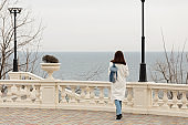 Young woman (brunette) in a white coat walks along the promenade.