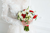 Bride holding bridal bouquet close up. red and white roses, freesia, brunia decorated in composition