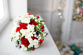 bridal bouquet close up. red and white roses, freesia, brunia decorated in composition