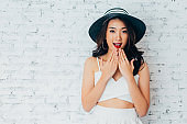 Young woman giving surprise look with fashionable summer hat over white wall background