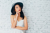 Young woman thinking about something with fashionable summer hat over white wall background with copy space