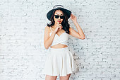 Asian woman holding fingers to her lips in fashionable dress and summer hat over white brick wall - Silent Shh gesture