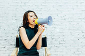 Asian business woman shouting with megaphone over white bricks wall background