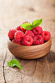 fresh raspberries in bowl over wooden background