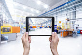 Futuristic machinery in production line & tablet