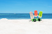 Ice cream popsicles and sunglasses on the white sandy beach
