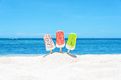 Colorful ice cream popsicles on the beach