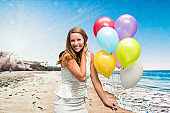 Smiling woman holding balloons at the beach
