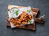 Grilled teriyaki chicken skewers and tzatziki sauce on a wooden board on a dark background, top view. Delicious appetizers