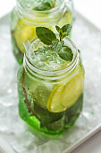 Tasty cold fresh drink lemonade with lemon, mint, ice and lime in glass on white table. Closeup.