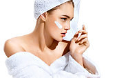 Young woman with flawless skin, applying moisturizing cream on her face.