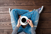 Woman drinking coffee while sitting on wooden floor