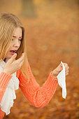 Sick ill woman in autumn park sneezing in tissue.