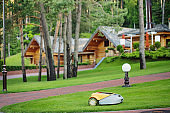 Robot lawn mower on background wooden houses