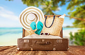 Retro luggage with summer beach holiday accessories placed on wooden planks