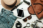 Top view / Flat lay accessory to travel with women / lady or female clothing concept.Essential item white mobile phone, watch,bag,hat,map,camera,necklace,trousers and sunglasses on white wood table.