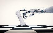 robotic hand holding chess king