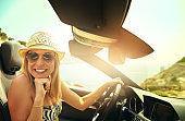 Cute woman driving convertible car
