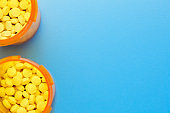 Pills In Two Prescription Medication Bottles On Blue Background