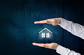 Property insurance concept. Home insurance and security concept. Protecting gesture of businessman and symbol of house and business background.
