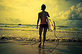 Young woman surfer with surfboard ready to surf