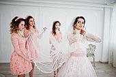 Fantastic bride posing in wedding dress with helpful pretty bridesmaids in big white room.