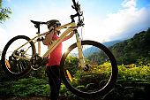 woman cyclist carrying mountain bike on sunrise summer forest trail