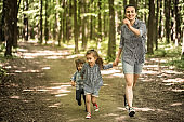 Mother with young daughters walk in the woods