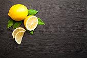 Lemon fruit on black slate background shot directly above