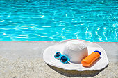 Summer hat, sunglasses and sunscreen near the pool