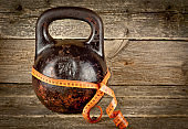 Vintage kettlebell on a wooden background with tape-measure