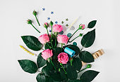 Pink roses with party confetti, noise makers and candles on a white background