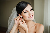Beautiful young bride with wedding makeup and hairstyle in bedroom Bride holds a beautiful wedding dress on trempel. Happy Bride waiting groom. Marriage Wedding day moment. Bride portrait