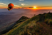 Hot air balloons floating up to the sky over mountain landscape
