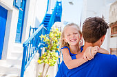 Happy dad and little adorable girl in greek village during summer vacation
