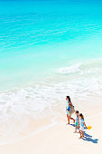 Adorable little girls and young mother on white beach. View to the family and ocean from above