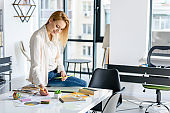 Confident girl sitting on table in office