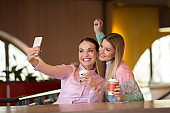 Happy girls having fun and taking selfies in a cafe