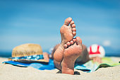 Sexy feet of young caucasian woman resting on beach