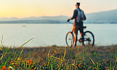 Unrecobnizable Man Cyclist Standing With Bike On Coast And Enjoying View of Nature Sunset Vacation Traveling Destination Resting Concept, Selective Focus