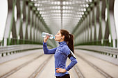 Young runner resting, drinking water on green steel bridge