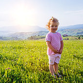 little girl runs through a beautiful meadow