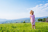 Little toddler girl running in a beautiful field