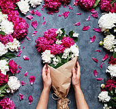 Top view of hands of young woman florist holding beautiful bouquet at flower shop. Florist at work: pretty woman making summer bouquet of peonies on a working gray table.