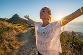 Young woman in Cape Town on top of mountain arms outstretched