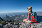 Young woman in Cape Town on top of mountain looking at view
