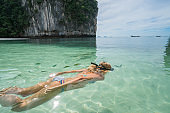 A woman snorkeling in the warm turquoise water of Thailand